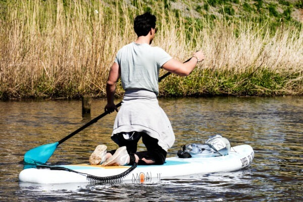 Supboard in het water op de knieën